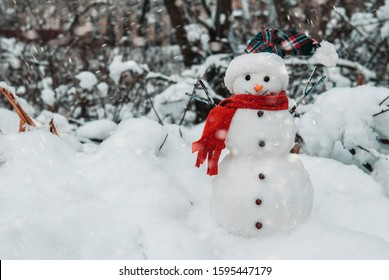 Snowman with cap and scarf in snowdrifts