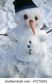Snowman with carrot nose, stocking cap. Melting has begun.
