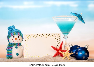 Snowman, cocktail and greeting card on sandy beach