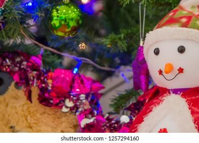 Snowman dolls, teddy bears and Christmas tree decorations.