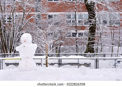 Snowman in an empty park or garden with fresh snoew, brick school building in the background.