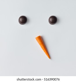Snowman face made of cookies and carrot. Minimal holiday concept. Christmas flat lay.