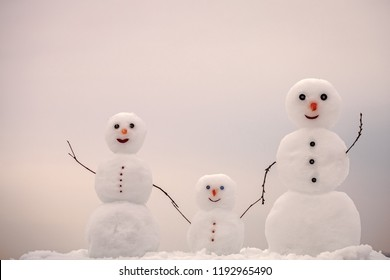 Snowman family in winter outdoor. New year mother, father and child from snow. Love and trust. Happy holiday and celebration. Christmas or xmas decoration.