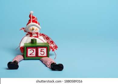A snowman figure is holding a box with two cubes forming a number twenty-five. It is December the twenty-fifth. It is Christmas day. It's the most beautiful time of the year!