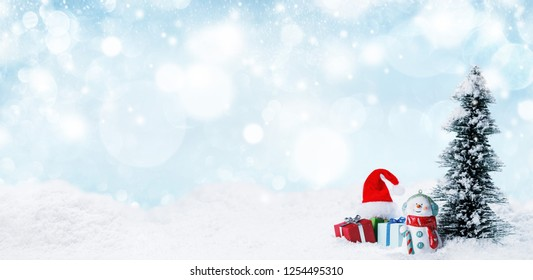 Snowman fir tree and christmas gifts on sleigh on snow, blue and white falling snow bokeh background