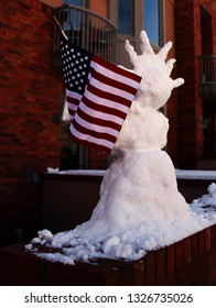 Snowman in the form of the Statue of Liberty with an American flag