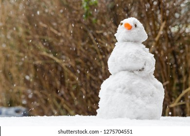 Snowman in garden on blurred bush background with fallen snowflakes. Low angle, close up crop