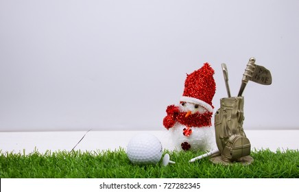 Snowman with golf bag are on green grass