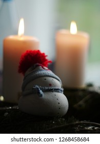 a snowman made of beton is sitting on a advent wreath in front of two candles. He wears a woolen cap with a red pompon
