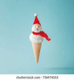 Snowman made of ice cream on bright blue background. Winter holiday concept.