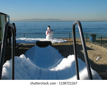 A snowman made of snow from the mountains stands beside the Pacific Ocean in southern California. An ice slide for children at a preschool makes it winter at the beach.
