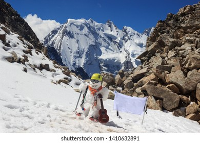 Snowman in mountaineer gear with ice ax, guitar and flag. Caucasus
