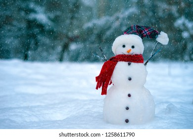 Snowman on a background of blue winter forest.