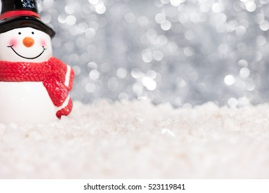 Snowman on snow over abstract blurred festive bokeh light glitter background with copy space