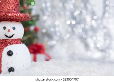 Snowman on snow over blurred christmas tree and gift box on glitter light bokeh background with copy space