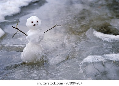snowman in puddle. bad warm rainy winter weather. melted snowman. anomaly weather concept. autumn, winter, spring seasons. copy space