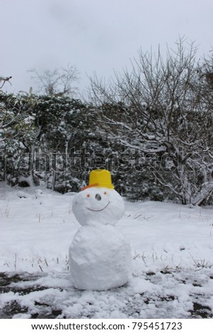 a snowman putting a yellow bucket on its head