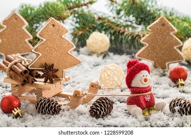 Snowman in a red cap on wooden table. Christmas or New Year composition with gifts and gingerbread cookies. Winter holiday composition.