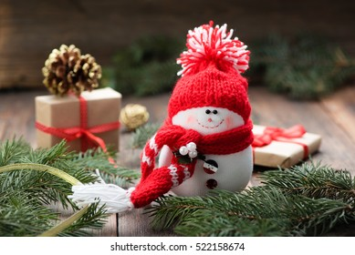 Snowman in a red cap on wooden table. Christmas decoration.