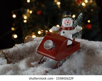 Snowman riding a red sled