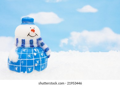 Snowman sitting on snow with a sky background, Snowman