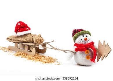 Snowman with sledge, Christmas tree and Santa Claus clothes isolated on a white background.
