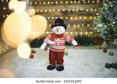 snowman in sweater standing in christmas lights
