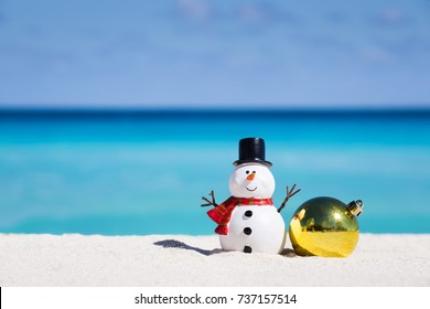 Snowman toy and christmas decoration ball at sandy beach on Caribbean sea background. New Year celebration