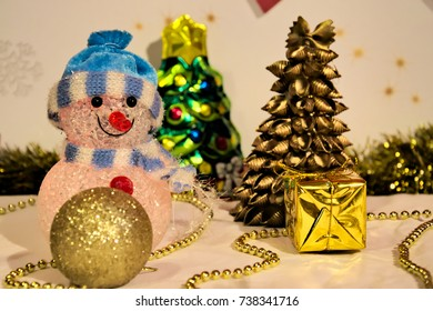 Snowman toy and few gold christmas accessories. Gold Christmas tree and Christmas tree ornaments / bauble.