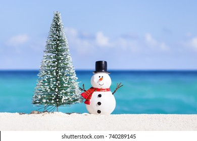 Snowman toy and fir tree at white sandy beach on Caribbean sea background. Christmas celebration