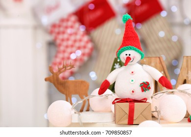 Snowman toy and gift box on table against blurred background
