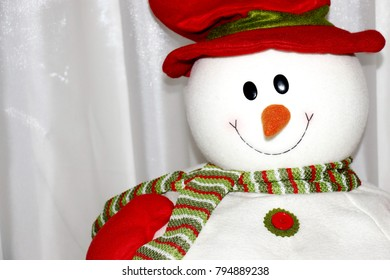 Snowman toy in a red hat close-up on white background