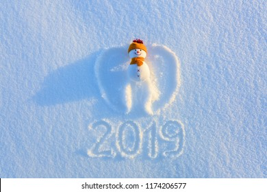 Snowman in yellow hat and scarf on the snow with drawn wings in yellow hat and scarf is laying on the snow. Writing 2019. Happy new year. Winter textured background.