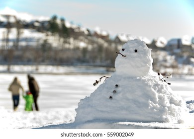 snowman and a young couple with a child unrecognizable in the background