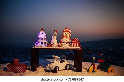 Snowmen Christmas tree, decoration toys. Toys in snow. Christmas presents from Santa. Snowmen wait for Santa and celebrate Christmas in mountains. New Year's mood. Merry Christmas and Happy New Year
