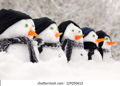 Snowmen close up in a row with hats and scarfs