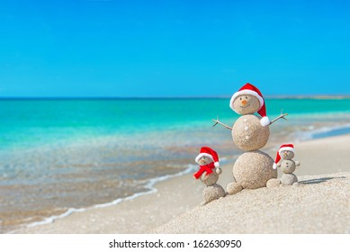 Snowmen family at sea beach in santa hats. New years and christmas holiday in hot countries concept.