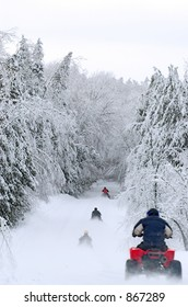 Snowmobile and ATV Riders on winter road.