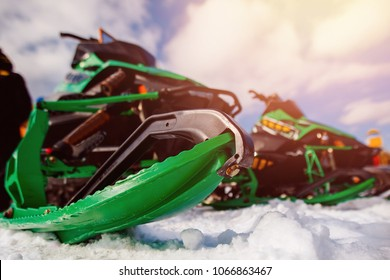 Snowmobile. Close-up of row of snowmobiles stand in snow, view from below, skiing.