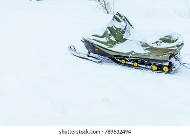 snowmobile covered by snow nobody near it