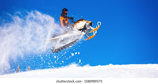 snowmobile jump straight up. the guy is flying and jumping on a snowmobile on a background of blue sky leaving a trail of splashes of white snow. bright snowmobile and suit. No brands. copy text