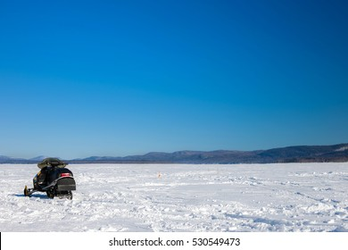 Snowmobile on frozen lake, with mountains in the background, ice fishing setup with tip-up's.