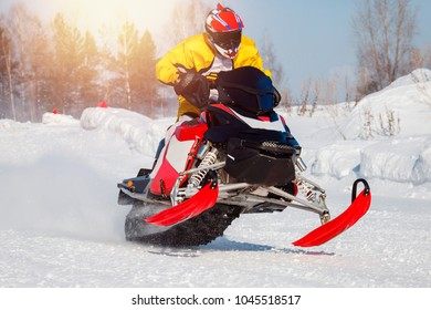 Snowmobile races jump in snow. Concept winter sports, racers.