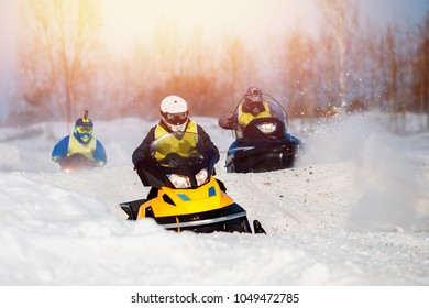 Snowmobile races in snow. Concept team of friends chasing mountains.