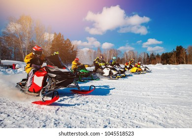 Snowmobile races start in snow. Concept winter sports, racers.