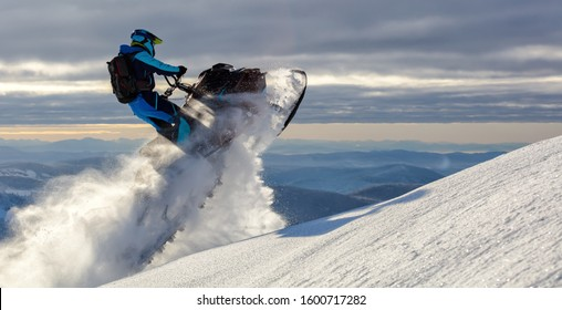 a snowmobile rider jumps in a mountain valley at dawn. sports snow bike with snow splashes and snow trail. bright snowmobile and suit without brands. snowmobilers sports riding. stock photo