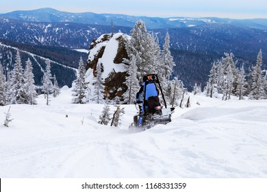 Snowmobile rides on snow-covered mountain. Winter landscape. View on top of Mountain Utuya in Kemerovo region, Sheregesh ski resort, March 2018.