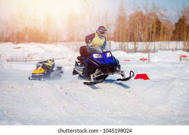 Snowmobile team of friends races in snow. Concept winter sports