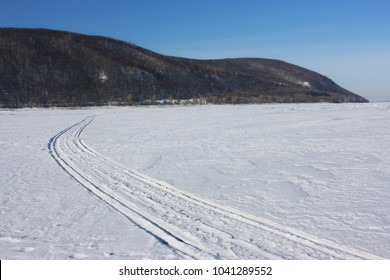 Snowmobile track marks on the snow of a frozen river against mountains and a blue sky