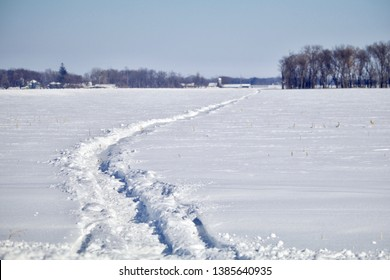 Snowmobile tracks head off into the blurry distance across the prairie snow.